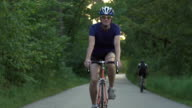 Young man Cyclist on road bike in sunset. Cycling video