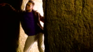 Young man dancing in the cave doorway video