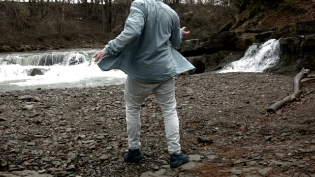 Young man dancing near a river in the mountains video