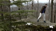 Young man dancing on a rock in the mountains. video