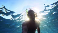 POV Man diving and sun shining through sea surface video