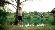 Young man doing backflip off rope swing video