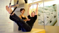 DOLLY: Young man doing pilates exercise with instructor video