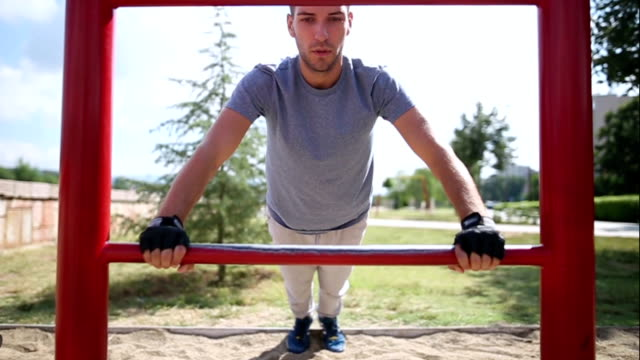 Young man doing push-ups on exercise equipment in park video