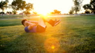 Young Man Doing Situps in the Park at Dusk Slow Motion video