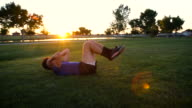 Young Man Doing Situps in the Park at Dusk video