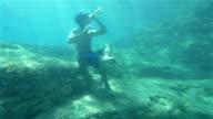 UNDERWATER: Young man drinking beer under water video
