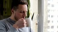 Young man drinking coffee and enjoying view from the window video