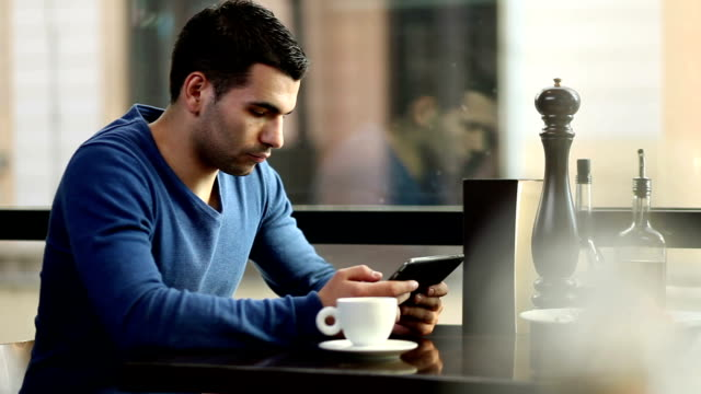Young man drinking coffee and using tablet video