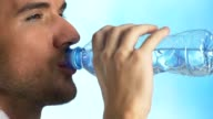 Young man drinking water from bottle video
