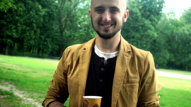 young man drinks tea and smiling on camera video