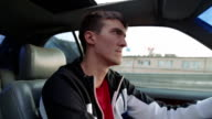 Young man driving a car. Inside shot video