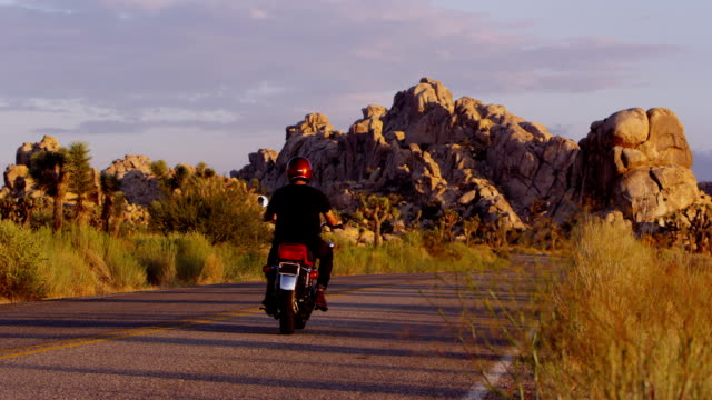 Young man driving motorcycle at sunset video