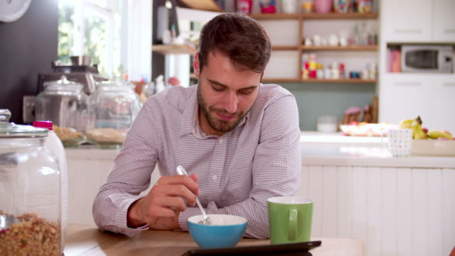 Young Man Eating Breakfast Whilst Using Digital Tablet video