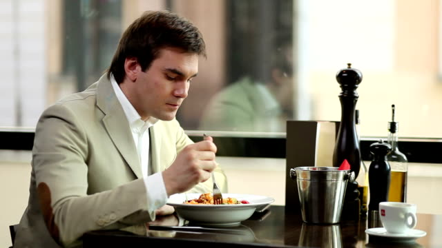 Young man eating in a restaurant. video