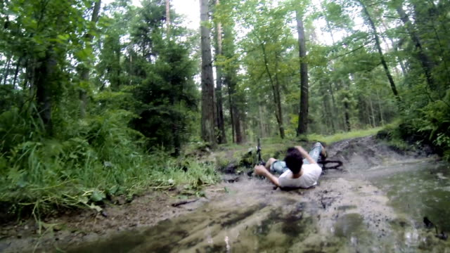 Young man falling down from the mountain bike into the dirty puddle. video