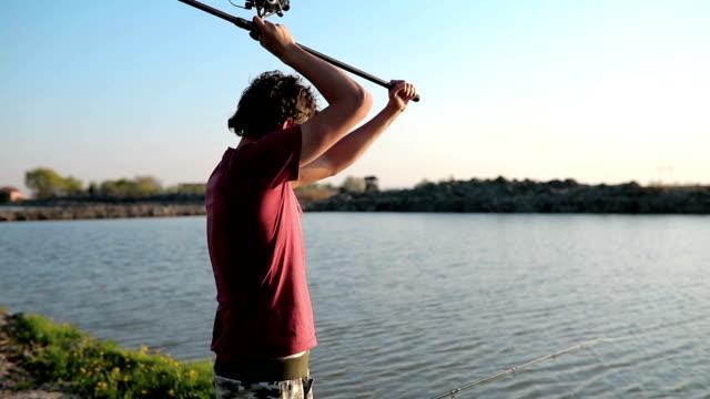 Young man fishing on a lake at sunset and enjoying hobby video