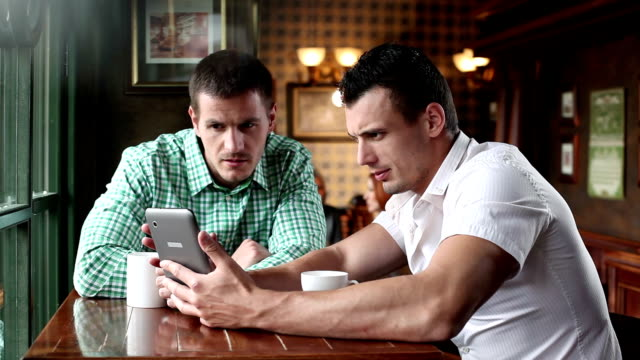 Young man friends in cafe using digital tablet video