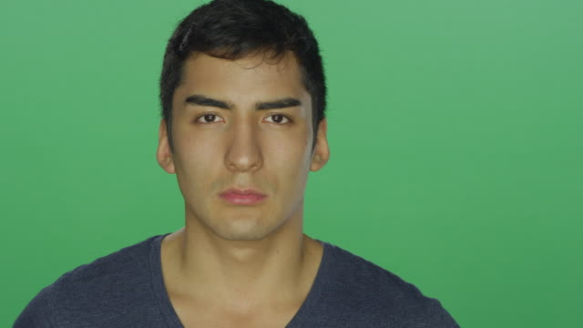 Young man frowns and looks sad, on a green screen studio background video
