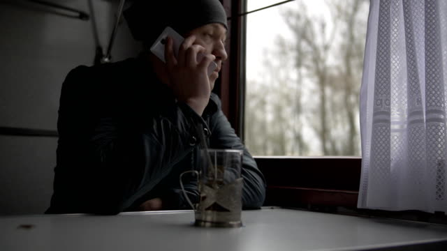 A young man goes on a train, answers a call, makes a call on a white smartphone, puts a smartphone on a table and takes a glass of tea, drinks video