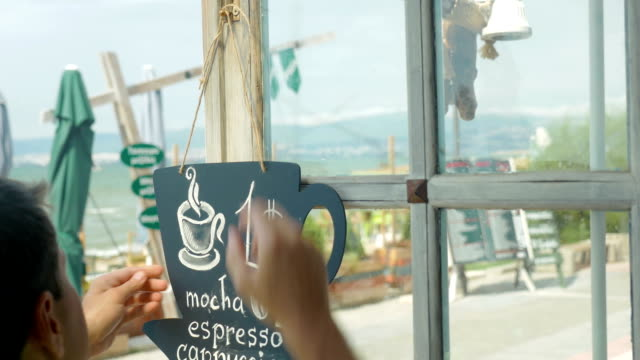 Young man hangs on the door of cafe black board in city of Perea, Greece video
