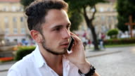 Young man have a serious talk on cellphone in the city center. Male in his 20s. video