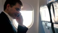 Young man having a business phone talk in plane video