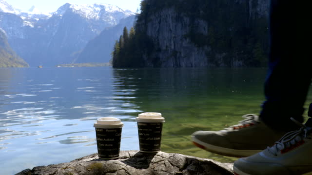 Young man having a cup of coffee in the morning next to the mountains lake. video
