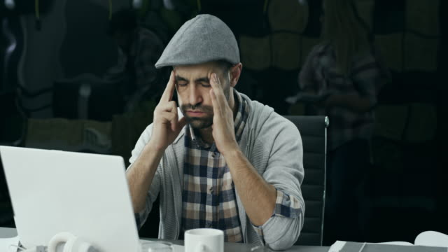 Young man having a headache at office video
