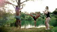 Young man having fun with friends jumping off rope swing into river video