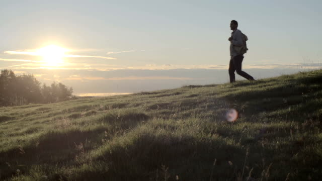 Young man hiking down mountain in outdoor nature scenery during summer sunrise or sunset - HD video footage video