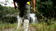 Young man hiking in tropical jungle forest with waterfall background video