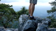 Young man hiking rock on cliff video