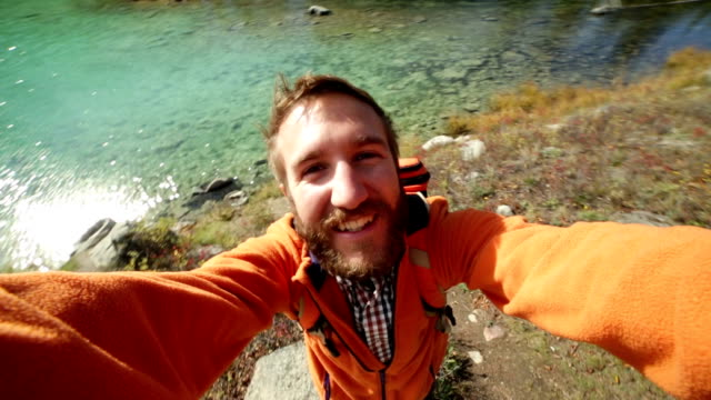 Young man hiking takes selfie by the lake video