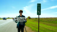 Young man, hitchhiker, trying to stop the car to Iowa on the highway in the Illinois, USA. video