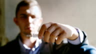 A young man holding a syringe with a drug. Concept: the willpower to quit drugs, danger, crime video