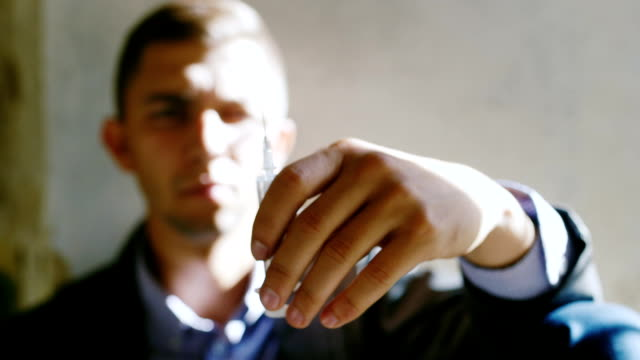 A young man holding a syringe with a drug. His face is blurred. Concept: risk of drug addiction, crime video