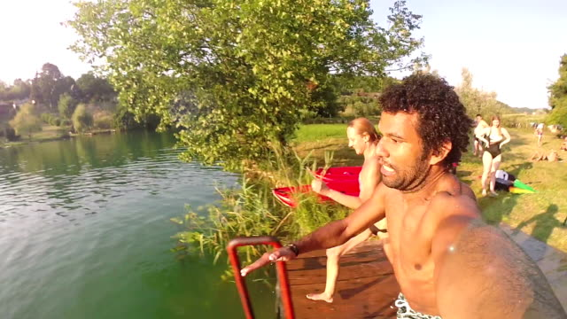 Young man holding camera while jumping into river with friends video