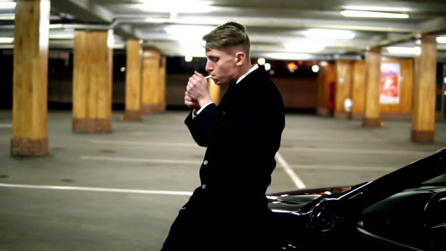 Young man in a black suit with a bow-tie smoking a cigarette sitting at the bonnet of the black car in the parking. Waiting for someone. video
