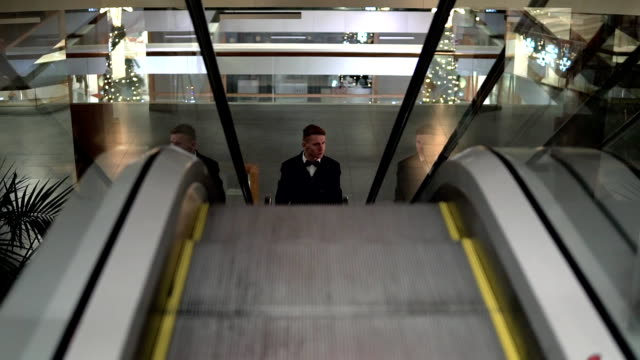 Young man in a black suit with bow tie coming up on the escalator in a shopping mall video