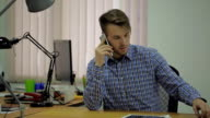 Young man in a blue plaid shirt sitting at his desk in the office and talking on a smartphone video