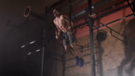 Young man in a good shape doing muscle-ups exercises on the sport rings at the gym video