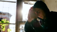 A young man in a hood sitting on a window. Praying or very thoughtful. In the rays of the sun video