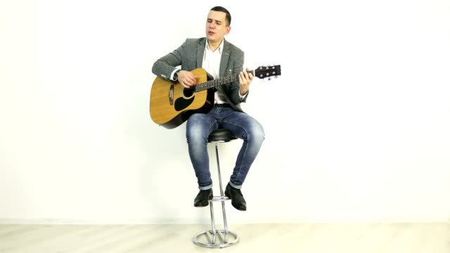 4K A young man in a jacket sits on a bar stool and plays an acoustic guitar. video