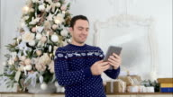 Young man in a knitted sweater taking selfies on a tablet netx to the Christmas tree video