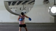 A young man in a shirt and shorts boxing outdoors. video