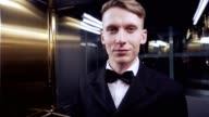 Young man in a suit with bow tie rides in the elevator looking in the camera and smiling. Evening event. video