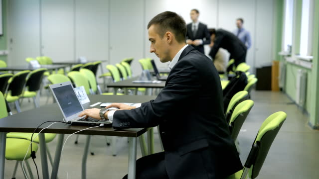 Young man in business suit with expensive wristwatch is working with the laptop sitting on green chair behind black desk in classroom with the group of people in the background video