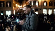Young man in downtown in the evening. Male use the smartphone standing on the square in crowd in city centre video