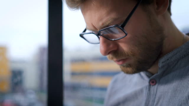 Young man in glasses sitting on a window sill in the hall while watching the news on the tablet video